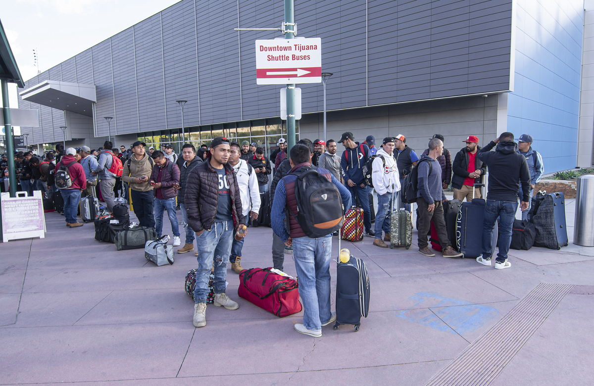 Migrant workers from Mexico wait for buses to transport them to seasonal work destinations